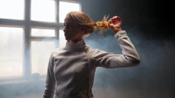 Thumbnail for A Young Woman Fencer She Lets Her Hair Down and Shakes Her Head Down and Back