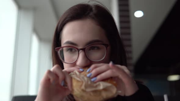 Thumbnail for A Young Woman Is Eating a Burger. A Girl Sits in a Cafe By the Panoramic Window and Eats Fast Food.