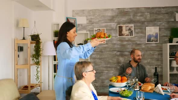 Thumbnail for Woman Bringing Roasted Chicken To the Table at Family Dinner