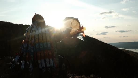 Slow Motion of the Silhouette of a Shaman with a Tambourine at Sunset.