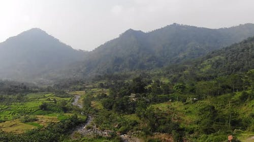 Aerial Video Clip of A Rice Paddy Valley with Mountains and dry river