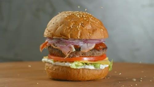 Weißer Sesamsamen, der in Zeitlupe in Brötchen fällt. Brötchen mit Sesam für die Herstellung von Hamburger.