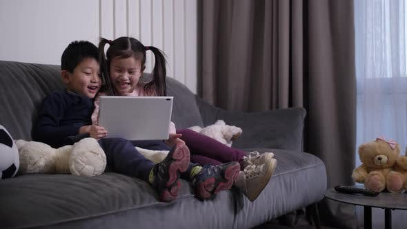 Thumbnail for Laughing Chinese Kids Watching Cartoons on Tablet