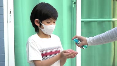 Asian Mother Spraying Sanitizer On Son Hands