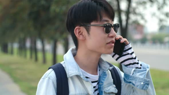 Thumbnail for Teenage Asian Boy Talking on Cell Phone on Street