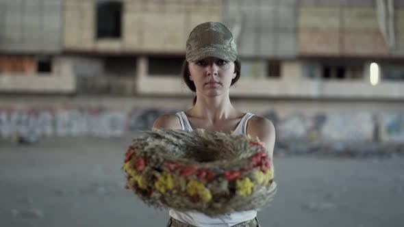 Thumbnail for Portrait of a Beautiful Girl in a Camouflage Cap and White T-shirt Holding a Wreath Looking