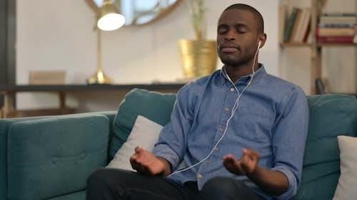Spiritual Young African Man Meditating on Sofa