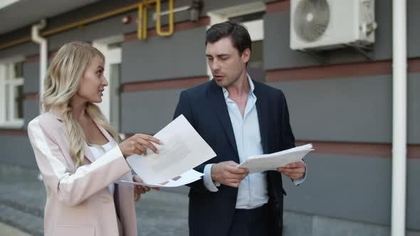 Thumbnail for Closeup Business Couple Discussing Documents. Partners Enjoy Success