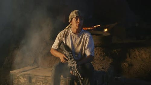 Teenager with Rifle Sitting in Trench