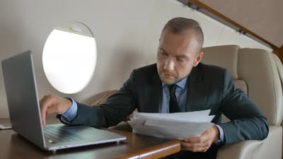 Handsome Male with Macbook Surfing in Internet Inside of Luxury Interior of Private Jet