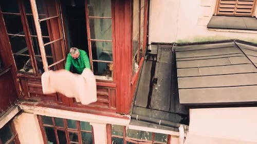 A man cleans a rug from the balcony of an old house