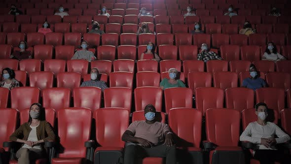 Diverse Masked Viewers Watching Movie in Cinema