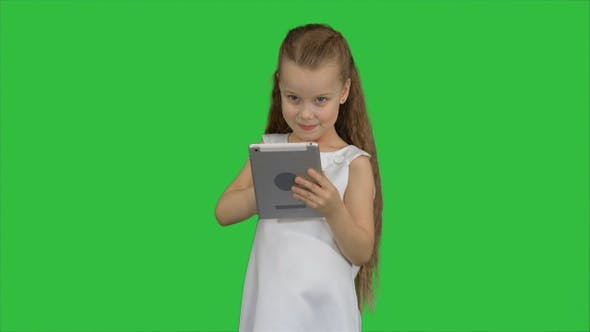 Cover Image for Small girl using tablet computer on a Green Screen, Chroma Key