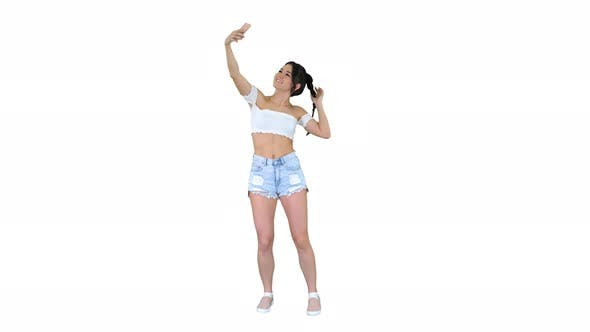 Thumbnail for Cute Brunette Girl Takes a Selfie and Dancing on White Background.