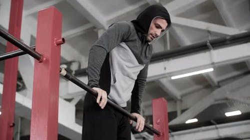 Athlete Man in Hoodie Pulling Up on Crossbar at Sport Training Gym
