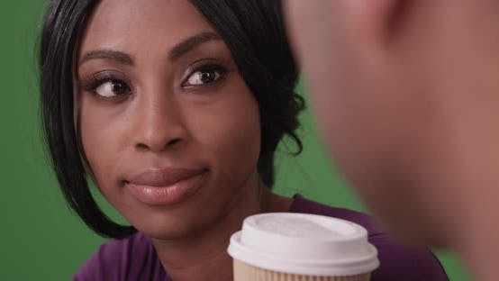 Thumbnail for Shot of black couple sitting in caf_ talking and drinking coffee on green screen