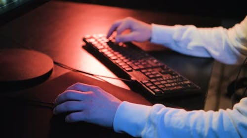Addiction Guy with Manly Hands Playing Video Game on Computer Screen with Fingers on Keyboard