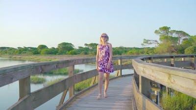 Blonde Girl Walks on a Wooden Walkway
