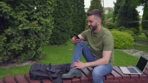 Thumbnail for Happy Bearded Man Talking on Cell Phone in Green City Park