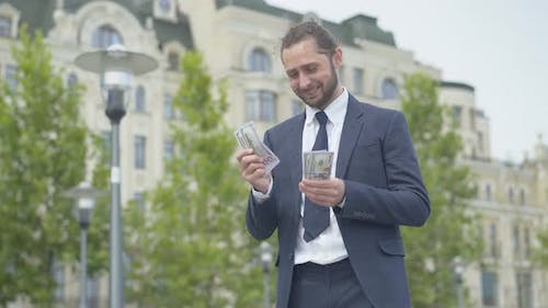 Confident Successful Rich Businessman Counting Dollars and Smiling. Portrait of Happy Caucasian
