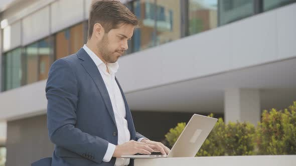 Thumbnail for Serious Businessman Using Laptop Outdoor