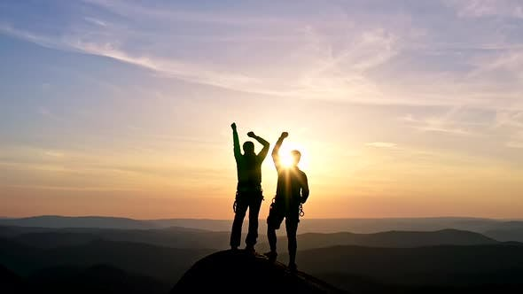 Silhouettes of a Happy Young Couple on Top of a Mountain Triumphantly Raising Their Hands in the Air