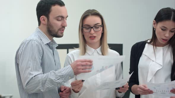 Thumbnail for Büroangestellte diskutieren Präsentationsmaterialien