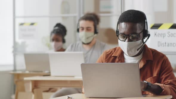 Thumbnail for Black Man in Face Mask Working on Laptop in Call Center