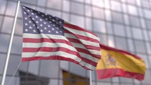 Flags of the USA and Spain in Front of a Skyscraper