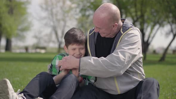 Thumbnail for Senior Man Sitting with His Grandson on the Blanket in the Park, Tickling the Little Boy