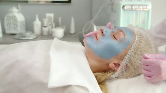 Applying A Cosmetic Mask On The Face In A Beauty Salon