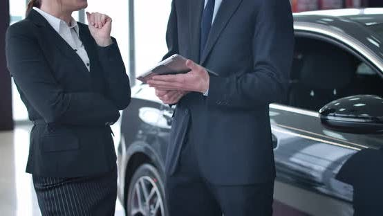 Thumbnail for Unrecognizable Caucasian Businesswoman in Suit Talking with Male Car Dealer with Tablet. Trader