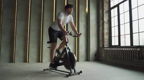 Muskulöser Mann, der Fahrrad im Fitnessstudio benutzt