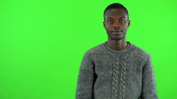 Thumbnail for A Young Black Man Smiles at the Camera and Applauds - Green Screen Studio