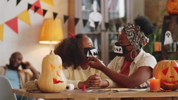 Black Mother and Daughter Drawing Vampire Teeth on Face Mask for Halloween