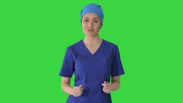 Thumbnail for Smiling Female in Blue Medical Uniform Advertising Clinic Services While Walking on a Green Screen