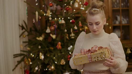 Thumbnail for Curious Woman Holding Christmas Present At Home