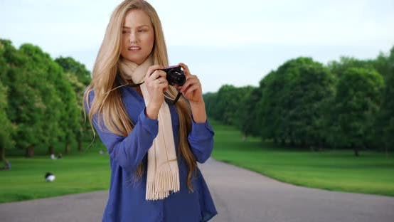Thumbnail for Young modern woman taking pictures on camera at public park