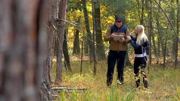 Thumbnail for A Hiking Couple Stands in the Middle of a Meadow in a Forest on a Sunny Day, He Reads a Map