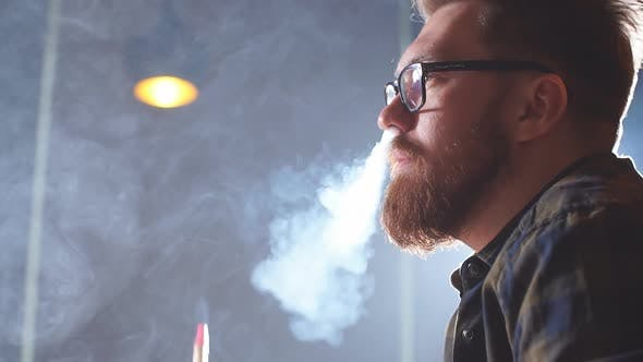 Attractive Man Exhaling Smoke From the Nose.