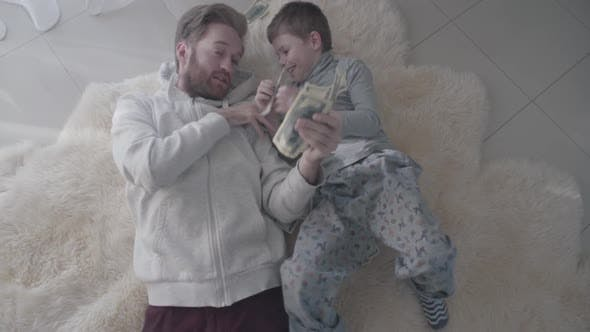 Thumbnail for Parent and Kid Collect Money Scattered on the Floor