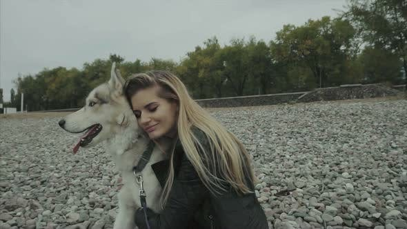 Young Cute Woman with Siberian Husky Dog Sitting on the Seaboard