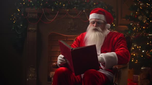 Thumbnail for Santa Claus Works on Christmas Eve Reading a Book in a Chair