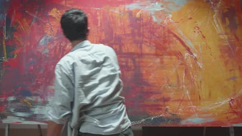 Male Artist Draws With His Hands On The Large Canvas, Using Hands Creates Colorful