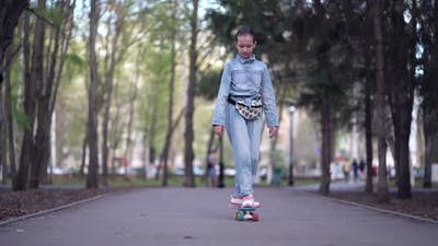 Fashionable Girl Travels Through Park Streets on a Skateboard