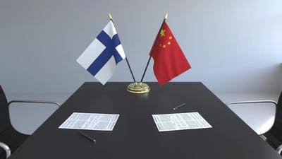 Flags of Finland and China and Papers on the Table