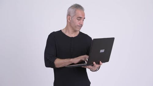 Happy Handsome Persian Man Thinking While Using Laptop