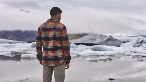 Man in Plead Shirt Admiring Beautiful Glaciers Melting By the Lake in Iceland