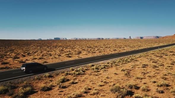 Thumbnail for Beautiful Aerial Shot of Minivan Car Driving Along Amazing American Desert Highway Road