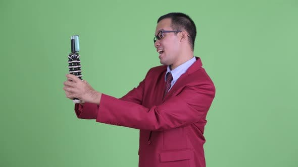Cover Image for Happy Asian Businessman Vlogging with Phone